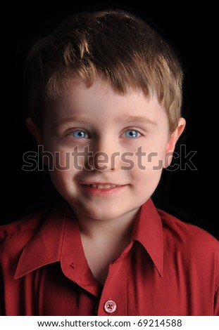A young three year old boy is against a black background with blue eyes and smiling.