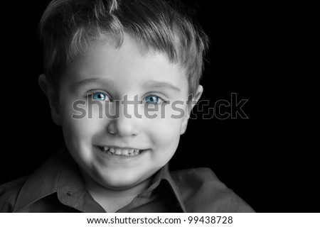 A young three year old boy is against a black background with blue eyes and smiling. Use it for a memory or growth concept.