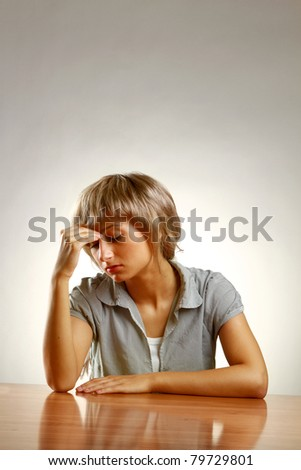 A young tired woman sitting at the desk, isolated on grey