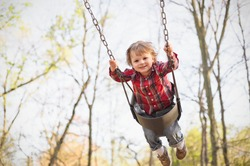 A young toddler boy swinging in the fall.