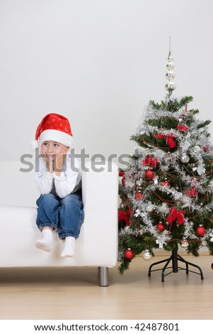 A young toddler boy wearing a Santa hat sitting on a white couch or sofa beside a decorated Christmas tree.