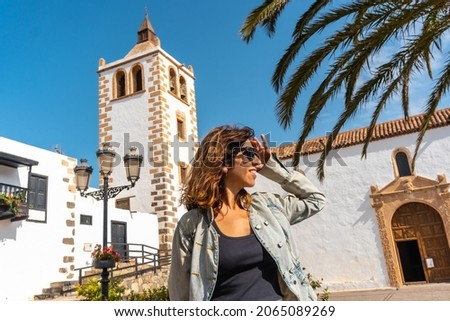 A young tourist enjoying the holidays next to the white church of Betancuria, west coast of the island of Fuerteventura, Canary Islands. Spain