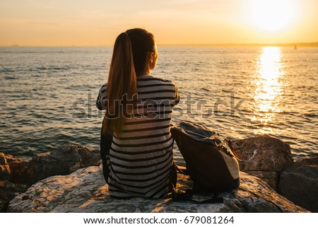 A young tourist girl with a backpack sits on the rocks next to the sea at sunset and looks into the distance. Rest, relaxation, travel, vacation. #679081264