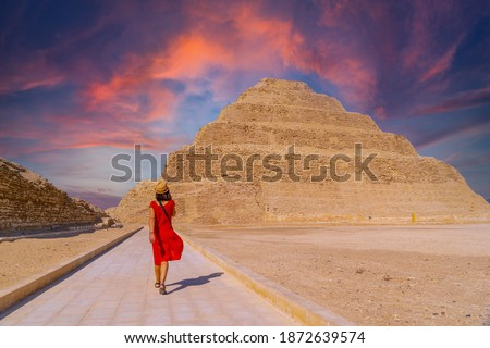 A young tourist in a red dress at the Stepped Pyramid of Djoser at sunset, Saqqara. Egypt. The most important necropolis in Memphis. The first pyramid in the world Stock photo ©