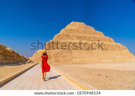 A young tourist in a red dress at the Stepped Pyramid of Djoser, Saqqara. Egypt. The most important necropolis in Memphis. The first pyramid in the world Stock photo ©