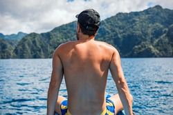 A young tourist man from a rare view sitting on a boat looks at the cliffs in Coron, Philippines