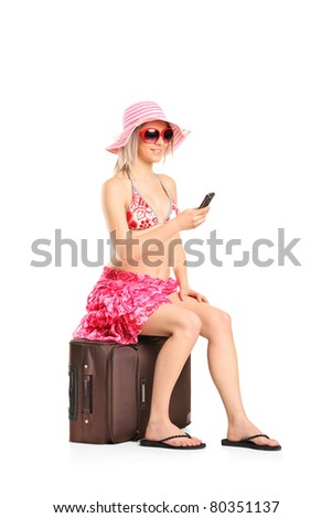 A young tourist woman typing a sms seated on a her luggage isolated on white background