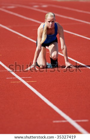 A young, track and field athlete on the starting block.