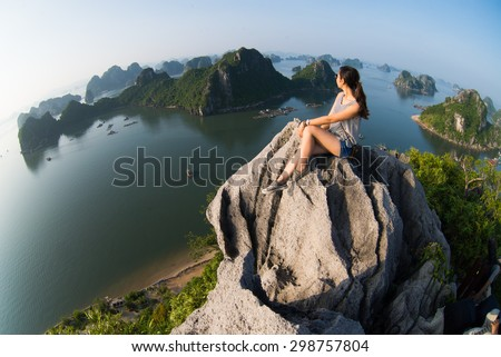 A young traveler girl sit on the top of mountain in Halong bay and enjoy the beauty of seascape.