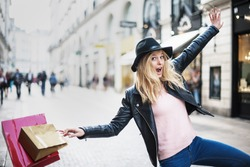 a young trendy woman doing shopping in the city expresses its joy in jumping and laughing