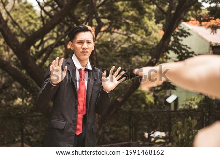 A young university student denies accusations made against him. The pointing hand of the accuser visible in photo. Foto stock ©