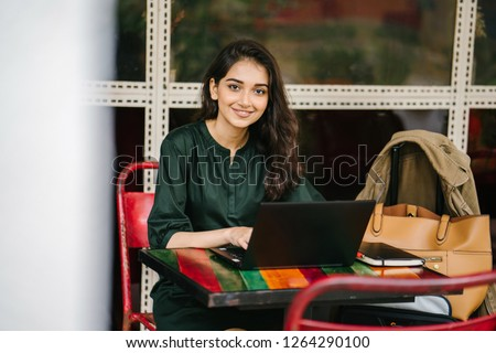 A young university student (Indian Asian woman) is studying and working on her laptop computer at a table during the day. She is attractive and beautiful.
