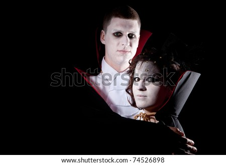 a young vampire couple posing together black background