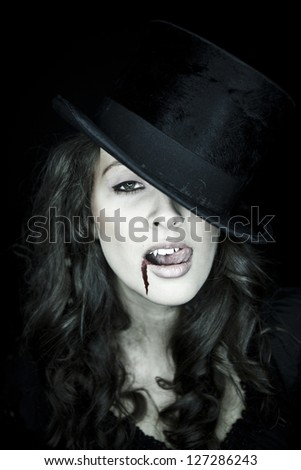 A young vampire girl with a black hat, blood is running out of her mouth