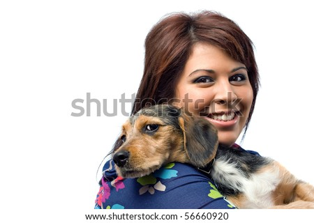 A young veterinarian holding a cute mixed breed beagle yorkie ( borkie ) dog isolated on a white background with copy space.