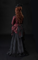 A young Victorian woman in a red and black bustle dress ensemble