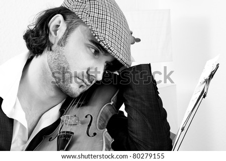 A young violinist studying his notes