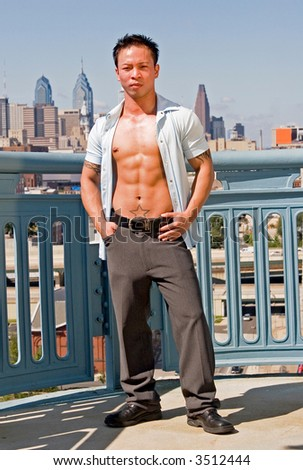 A young well built man in front of the Philadelphia skyline