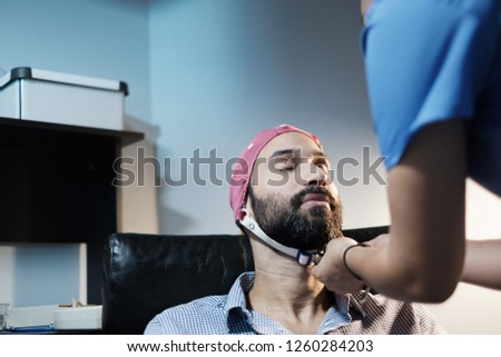 A young white bipolar man with visits a clinic for an electroencephalogram. Medical staff performs an EEG on Caucasian bearded male. Moment when cap is put on. Mental health and disease #1260284203