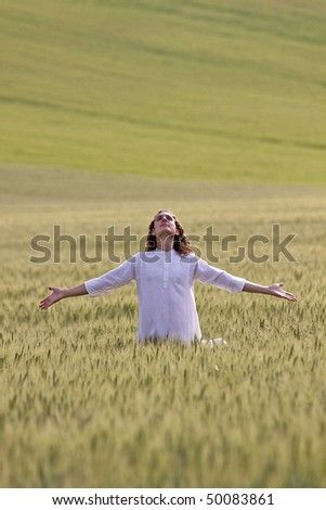 A young white dressed man stands in a field of cereal plants in a faithful and positive posture with outstretched arms