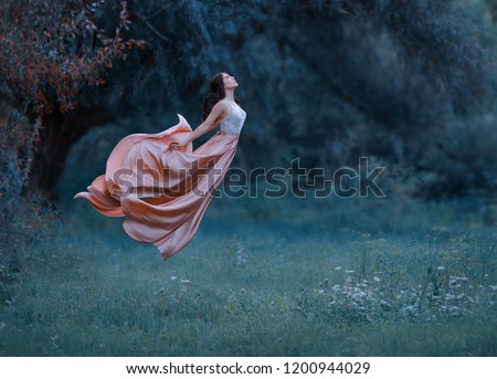 A young woman, a mysterious witch is floating in the air like a butterfly. A luxurious, long dress waving in the wind. Cold forest background. Enchanted princess. Art photo of levitation