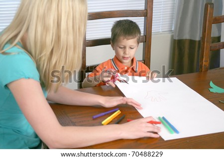 A young woman and a child cutting paper with scissors