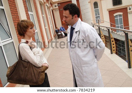 A young woman and a male doctor stand outside a building, having a conversation.