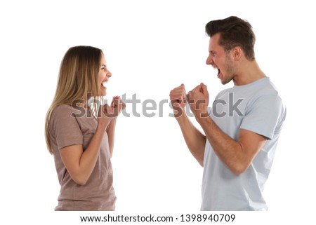 A young woman and a young man look happy and clench their fists