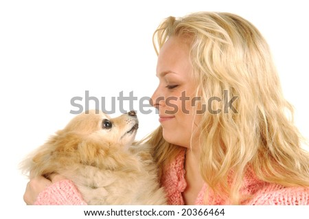 A young woman and her pomeranian gaze at one another.