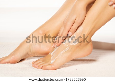 a young woman applies lotion to her feet on white towel Stockfoto ©