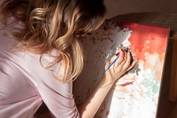 A young woman artist paints a picture by numbers. Sunny day. Creativity and art relieve stress. Hobby at home. Calming, relaxing, meditation. Self-isolation. Lock down. Introvert