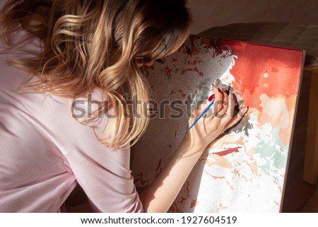 A young woman artist paints a picture by numbers. Sunny day. Creativity and art relieve stress. Hobby at home. Calming, relaxing, meditation. Self-isolation. Lock down. Introvert Foto stock ©