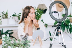A young woman beauty blogger broadcasts live streaming to review makeup and cosmetic products on social media,reviews beauty product for video blog.Influencer uses smartphone on tripod and ring lamp.