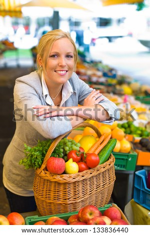 a young woman buying fruits and vegetables at a market. fresh and healthy food.