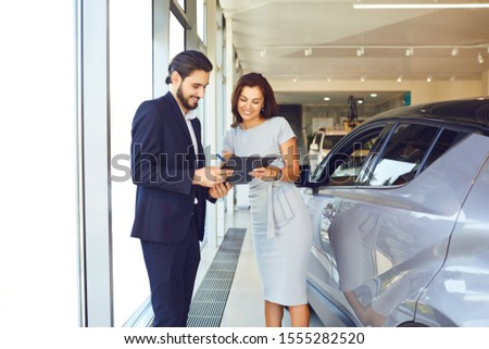 A young woman buys a new car in an auto salon #1555282520