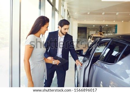 A young woman buys a new car in an auto salon #1566896017