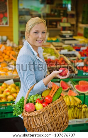 a young woman buys fruits and vegetables at a market. fresh and healthy food.
