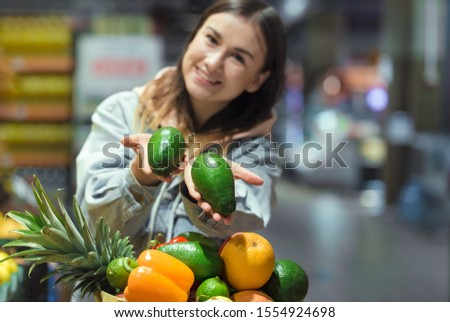 A young woman buys groceries in a supermarket. Health food. Healthy food, organic food.