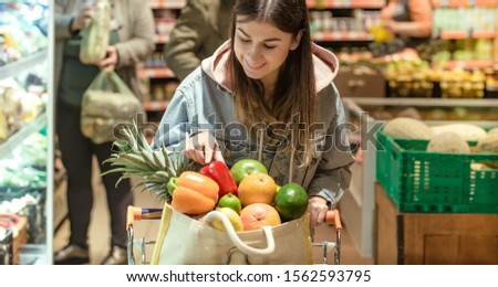 A young woman buys groceries in a supermarket. Health food. Healthy food, organic food. #1562593795