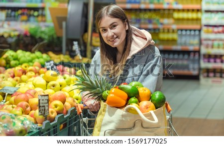 A young woman buys groceries in a supermarket. Health food. Healthy food, organic food. #1569177025