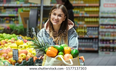 A young woman buys groceries in a supermarket. Health food. Healthy food, organic food. #1577137303