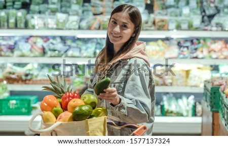 A young woman buys groceries in a supermarket. Health food. Healthy food, organic food. #1577137324