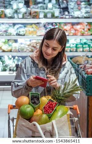 A young woman buys groceries in a supermarket with a phone in her hands. Health food. #1543865411