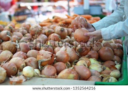 A young woman chooses and buys onions in a supermarket in the vegetable department.