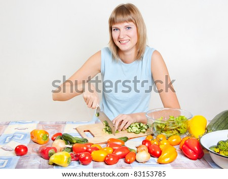 A young woman chops vegetable salad