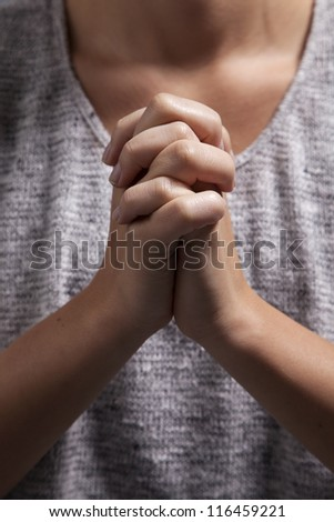 A young woman clasps her hands in prayer.