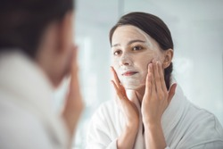 A young woman cleansing her face
