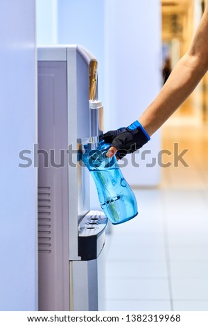 A young woman collects water from the cooler in bottle to quench her thirst after long intense workout. Close-up of hand in sports glove holding blue transparent bottle. Stock photo ©