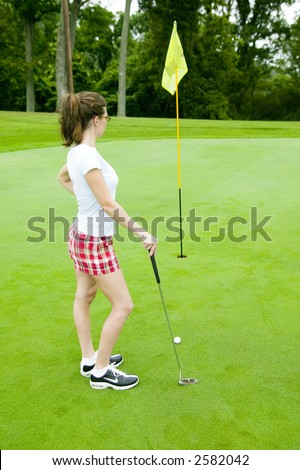 A young woman considers her shot on the putting green of a golf course.  Model Released.