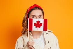 A young woman covers her face with a small flag of Canada, Canada Day celebration. Student girl holding the flag of Canada, education abroad